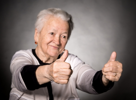 Old woman showing ok sign on a gray background photo