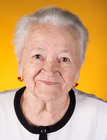 Portrait of smiling old woman on a yellow background 免版税图像