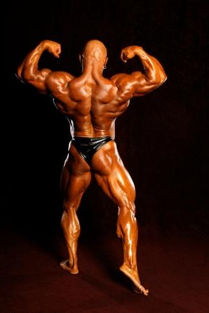 The bodybuilders back ona dark background.
