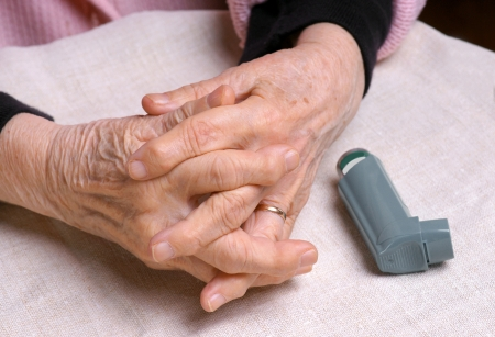 Senior womans hands and asthma inhaler photo