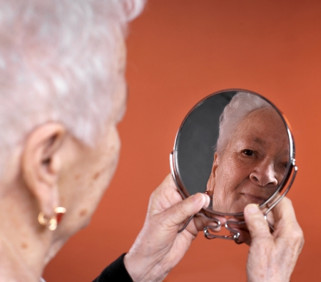 Portrait of old woman looking into a mirror, with focus set on the mirror image.