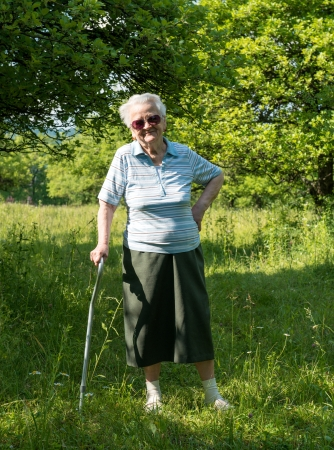 eighty: Old woman standing with a cane on nature background