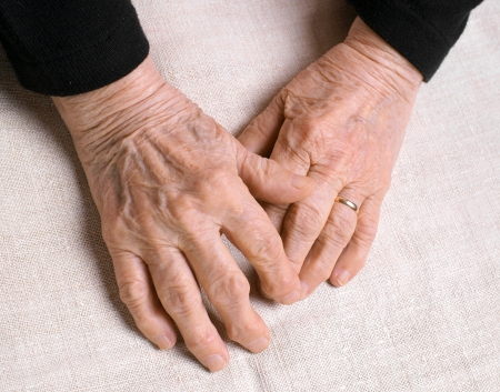 Old womans hands on a white background photo