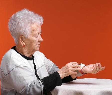 arterial: Old woman measures arterial pressure on an orange background