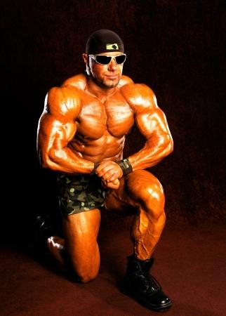 Bodybuilder posing on a dark background Banco de Imagens