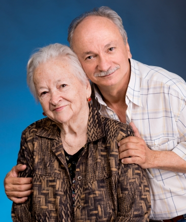 beloved: A grown son with his aging mom on a blue background