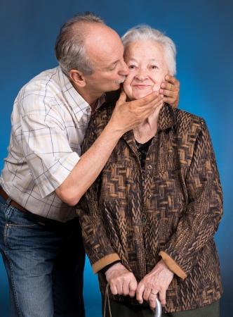 madre hijo: Un hijo adulto que besa a su madre envejecimiento sobre un fondo azul