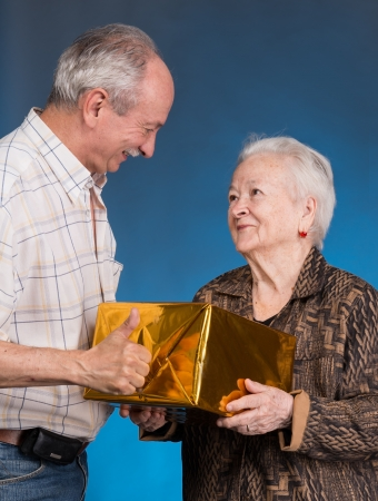 A grown son and aging mom with present box on a blue background 免版税图像