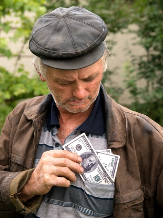 The farmer with money in his jacket on natural background photo