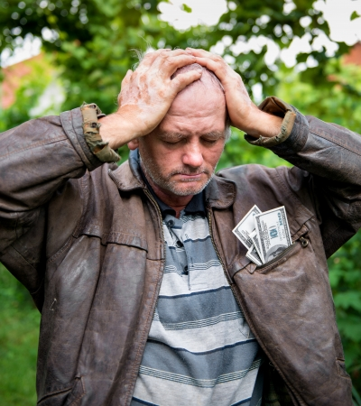 Stressed farmer with money in his jacket on natural background photo