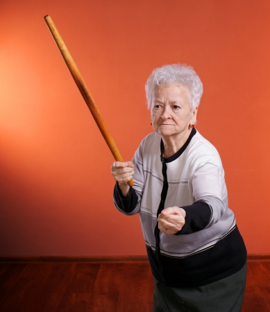 Old angry woman threatening with a rolling pin  on orange background