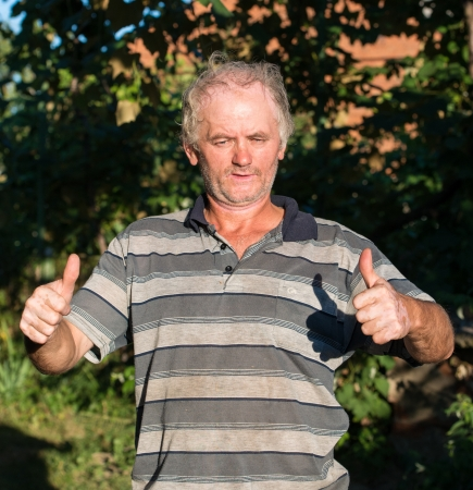 Senior poor man showing yes sign on natural background photo