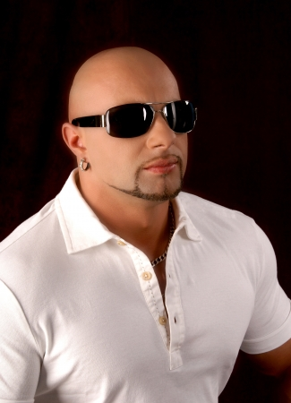 Bald guy wearing fashion sunglasses on a dark background photo