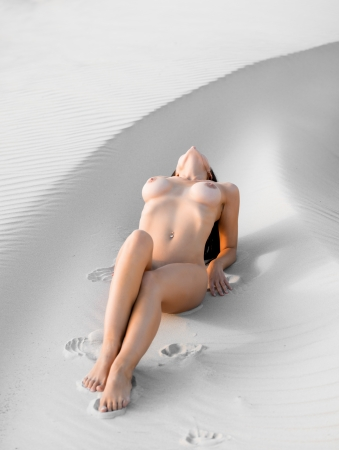 naked women body: Young nude woman lying on the sand Stock Photo