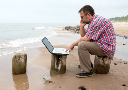 Tired senior businessman sitting with notebook on beach photo