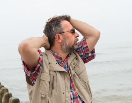Elderly man suffering from headache on the sea background photo