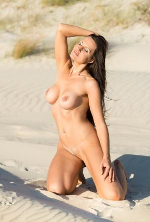 nue plage: Jeune femme nue posant sur la plage