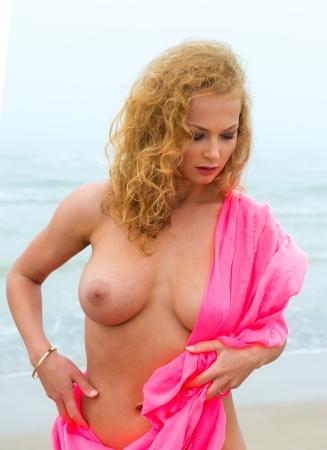 Pretty nude woman posing in pink fabric in morning fog