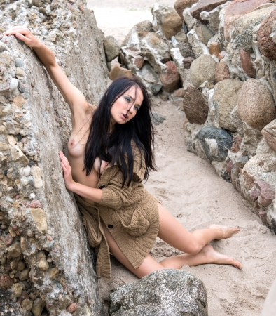 Naked emotional woman posing near the ruins of the old fortress