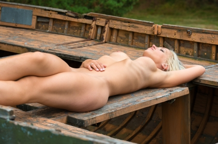 Young nude woman posing in a boat against the nature background