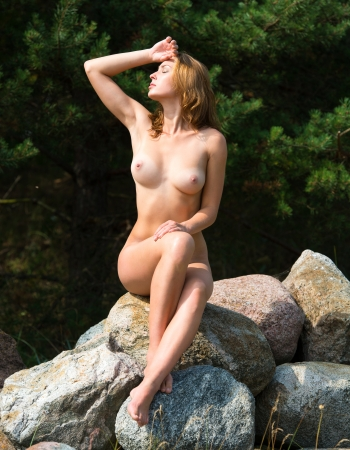 Beautiful nude woman posing on stones against nature background