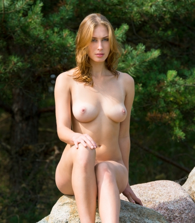 nude: Beautiful nude woman posing on stones against nature background