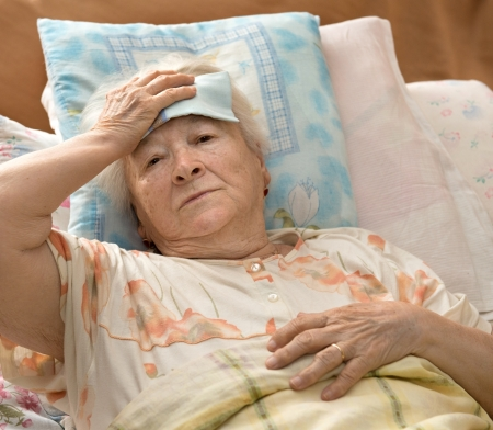 Sick senior woman lying at bed Banco de Imagens
