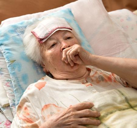 Sick senior woman lying at bed photo