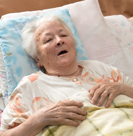 Sick senior woman lying at bed Standard-Bild