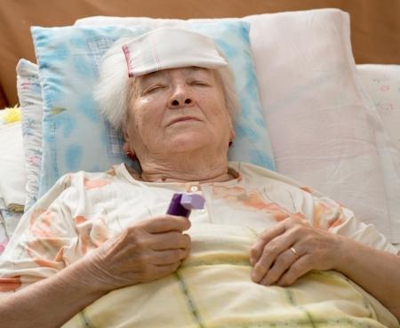 Zieke hogere vrouw liggend op bed Stockfoto