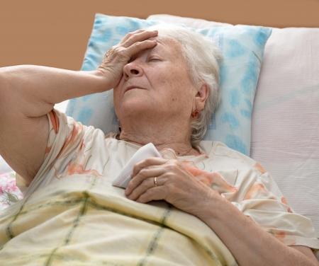 Sick senior woman lying at bed Stock Photo