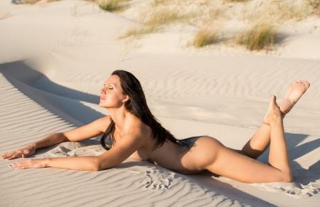 naaktstrand: Jonge vrouw naakt zonnen op het strand