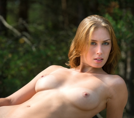 Beautiful nude woman posing  against nature background