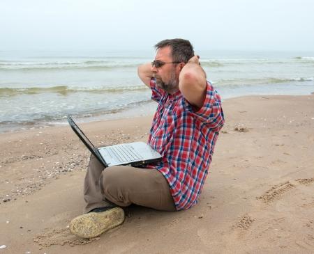 Senior businessman sitting with notebook on beach photo