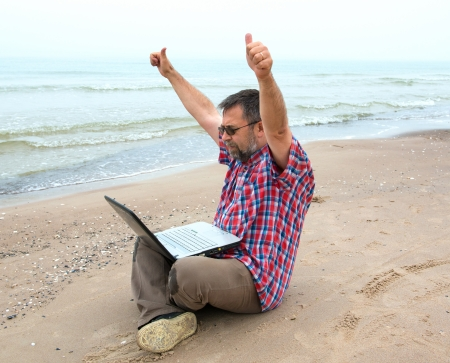 Emotional elderly businessman with laptop on the beach photo