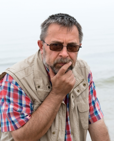 Pensive and sad looking elderly man on the beach Stock Photo - 21445549