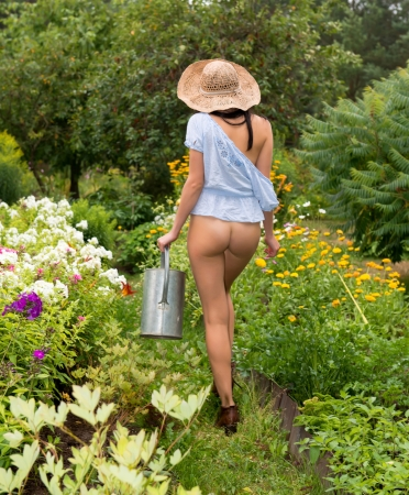 hat nude: Young nude woman with watering can in the garden