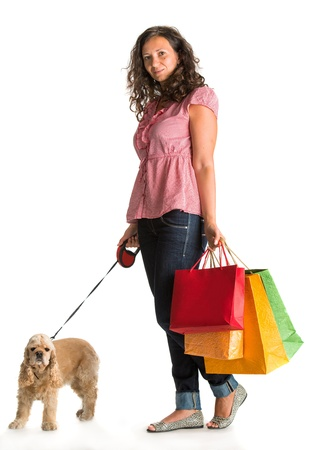 Curly woman with shopping bags and american spaniel on a white background photo