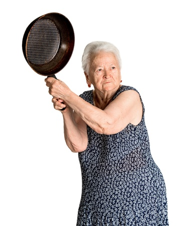 Angry old woman with a pan on a white background 免版税图像