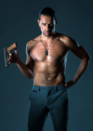 sexy police: Handsome man with a gun on a gray  background Stock Photo