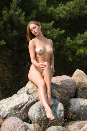 Beautiful nude woman sitting on stones against nature background