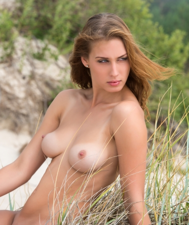 hot breast: Young naked woman posing on natural background in the sunlight Stock Photo
