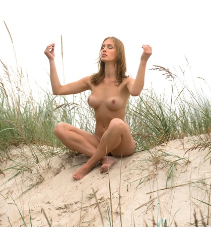 nude breast:  Yoga Time  Young woman sitting naked on sand on a foggy day