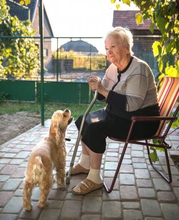 Oude vrouw zit op een stoel met een stok in de tuin Stockfoto