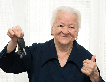 Old woman holding car key and making OK gesture