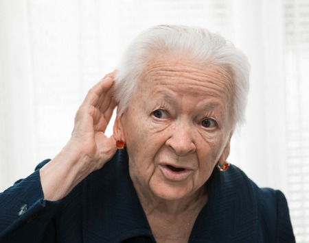 Portrait of old woman putting hand to her ear  Bad hearing photo