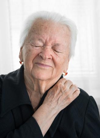 Oude vrouw die lijden aan schouder pijn Stockfoto