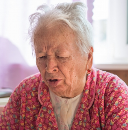 Portrair of old coughing  woman  photo