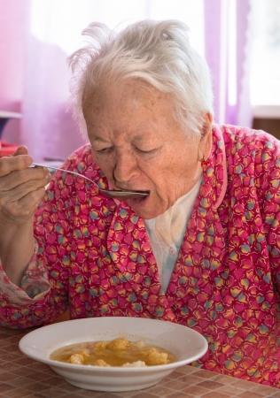 Oude vrouw het eten van soep