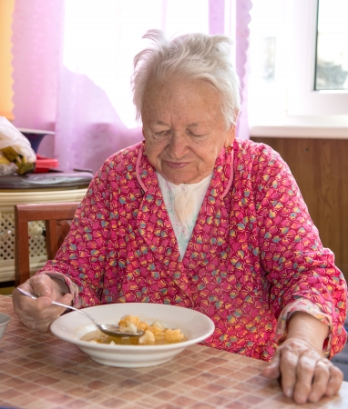 Old woman eating soup photo